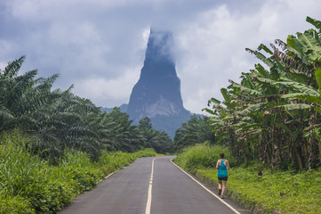 Runner on a road leading to the unusal monolith, Pico Cao Grande, east coast of Sao Tome, Sao Tome and Principe, Atlantic Ocean, Africa