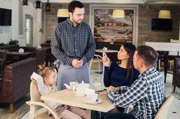 restaurant and holiday concept - waiter giving menu to happy family at cafe