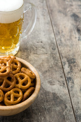 Pretzels in bowl and beer on wooden table