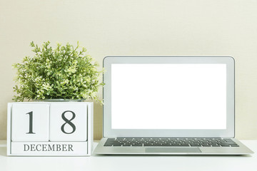 White wooden calendar with black 18 december word with white blank space at center of computer notebook on white wood desk and cream wallpaper textured background , selective focus at the calendar