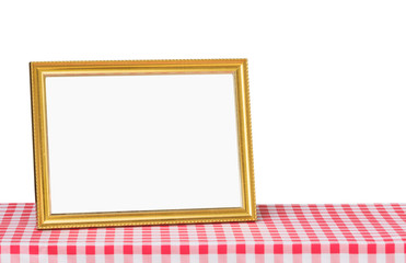 Golden picture frame on red fabric tabletop with copy space.