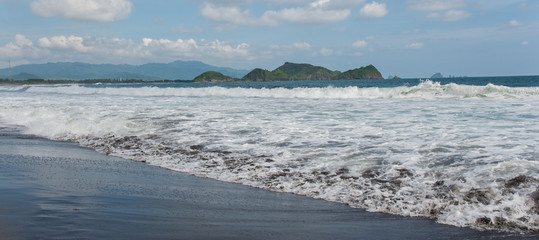 Ocean Beach with foaming waves on the background of rocks and mountains (Indonesia)