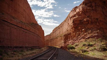 railroad tracks between high rock walls