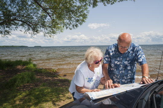 Senior Caucasian couple in their 70s study a map on the hood of their car parked near a lake in northern Minnesota