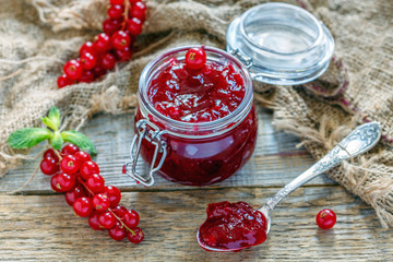 Teaspoon and glass jar with red currant jam.