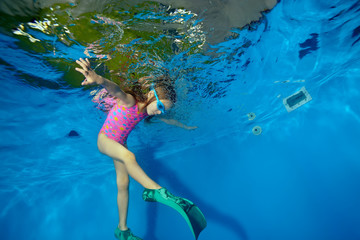 Little girl plays sports and swims with fins underwater in the pool on a blue background. Portrait. The view from under the water at the bottom. Landscape orientation