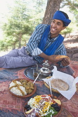 Young Berber man eating typical Berber lunch of rice and kafta in sauce, salad, fresh bread and mint tea at a picnic in Ait Mizane valley, High Atlas Mountains, Morocco, North Africa, Africa