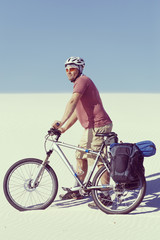 Traveling man on a bicycle in the desert.