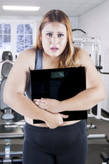 Obese female with weight scale on fitness center