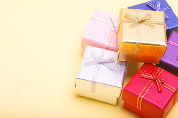 Group of colored Gift boxes with bows on a yellow background