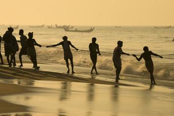 Fishermen hauling in nets at sunrise, Chowara Beach, near Kovalam, Kerala, India, Asia