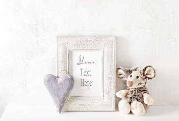 An arrangement of a mascot, wooden heart and a picture frame