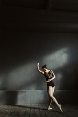 Young gymnast dancing in the dark lighted room
