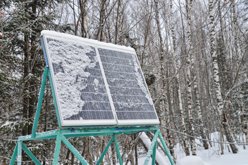 Solar panel plant under the snow in winter forest