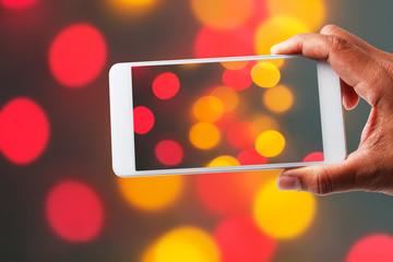 Hand holding Image shooting photograph bokeh with smartphone