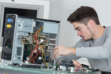 Young computer repairman at work