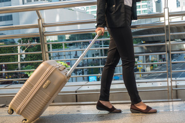 travel business woman pulling suitcase bag walking along in the