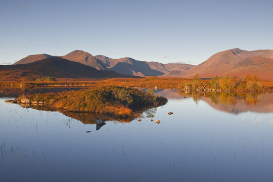 Lochan na h-Achlaise reflecting the surrounding mountains on Rannoch Moor, a Site of Special Scientific Interest, Scotland