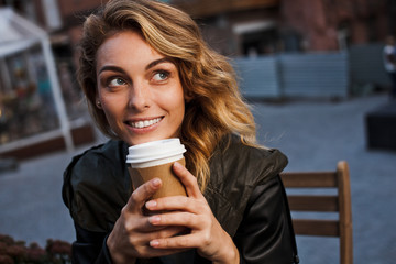 Young beautiful woman drinks coffee on cafe terrace