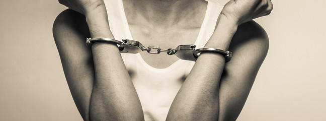 closeup young woman with handcuffs, violence or internment concept background