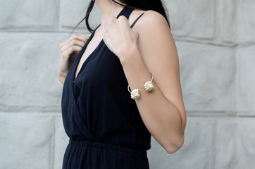 Fashion woman in black sleeveless dress wearing stylish bracelet
