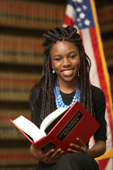 Portrait of a young attractive African American woman.  Woman lawyer in law library.