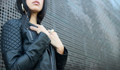 Woman wearing leather jacket posing by the wall. Beauty, fashion concept.