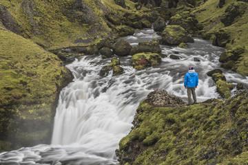Tourist at waterfall above Skogafoss Waterfall, Skogar, South Region, Iceland