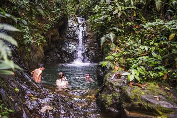 Tourists swimming under Cucharillos Waterfall, Choco Rainforest, Mashpi Cloud Forest, Pichincha Province, Ecuador, South America
