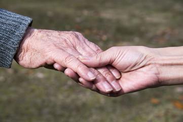 介護する老人と娘の手のアップ