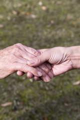 介護する老人と娘の手
