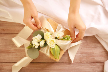 Female hands making gift box with flowers on wooden table