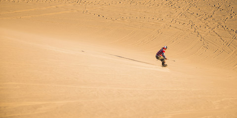 Sand boarding on dunes in the desert at Huacachina, Ica Region, Peru, South America