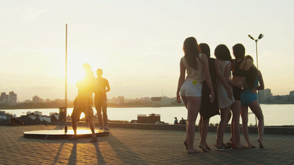 The photographer photographing group of beautiful girl at sunset