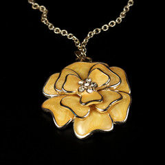 Yellow pendent in the form of a flower, costume jewelry, close up on a black background.