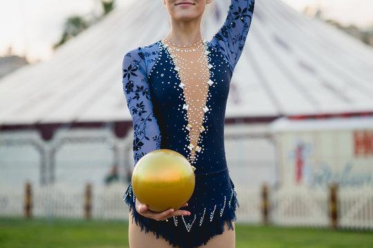 Crop gymnast holding ball