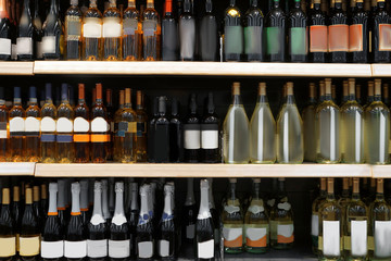 Shelves with alcohol bottles in supermarket