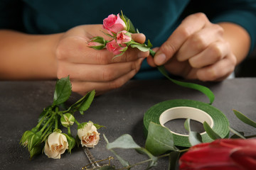 Female hands making beautiful bouquet of flowers on dark background