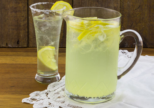 Margarita in glass pithcher with glass and lemon slices on wood table
