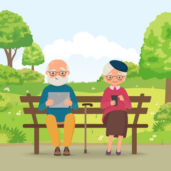 Elderly couple in the park with gadgets