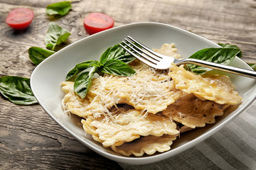 Plate of ravioli with cheese on table