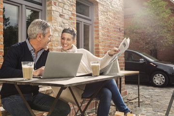 Happy mature couple reading newspaper with laptop in back yard