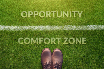 Top view, Male with Leather Shoes with a word : Comfort Zone and Opportunity between a line on Green Grass Field, Making Decision in Life