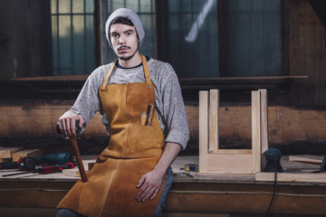 Portrait of carpenter holding hammer while sitting on bench at workshop