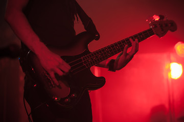 Silhouette of bass guitar player on red