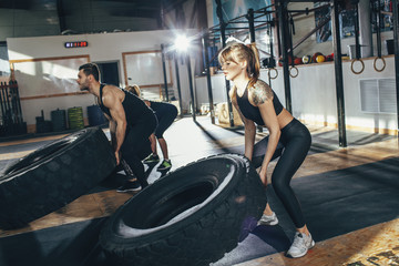 Determined male and female athletes flipping tire at health club