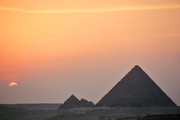 Dramatic sunset behind distant Egyptian pyramids in Giza, Cairo, Egypt