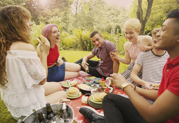 Cheerful friends having food during party at yard