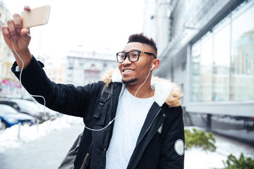 African cheerful man make a selfie while listening music outdoors.