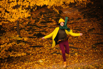 beautiful young woman jumping outdoors in autumn